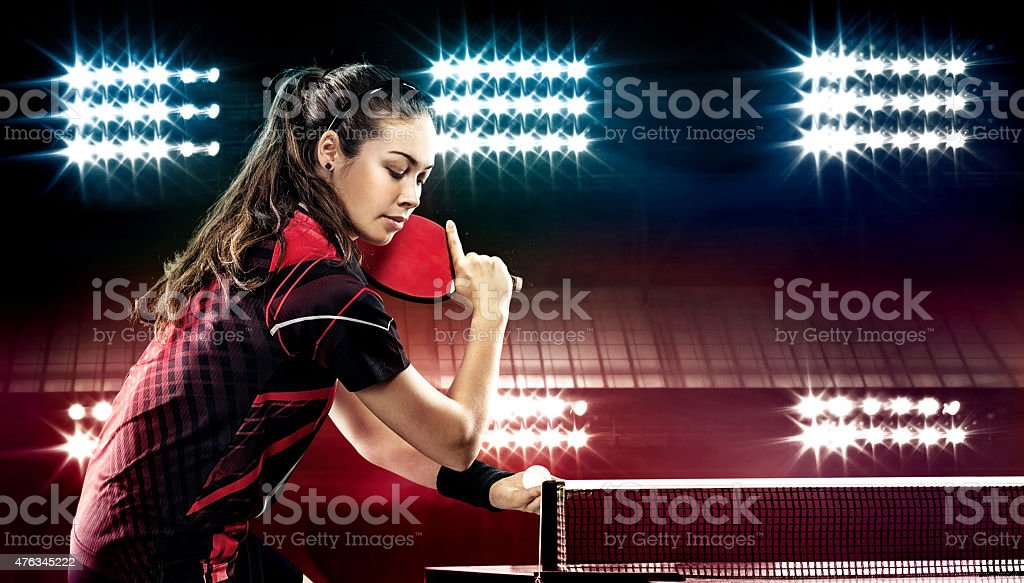 Young pretty sporty girl playing table tennis on black background stock photo