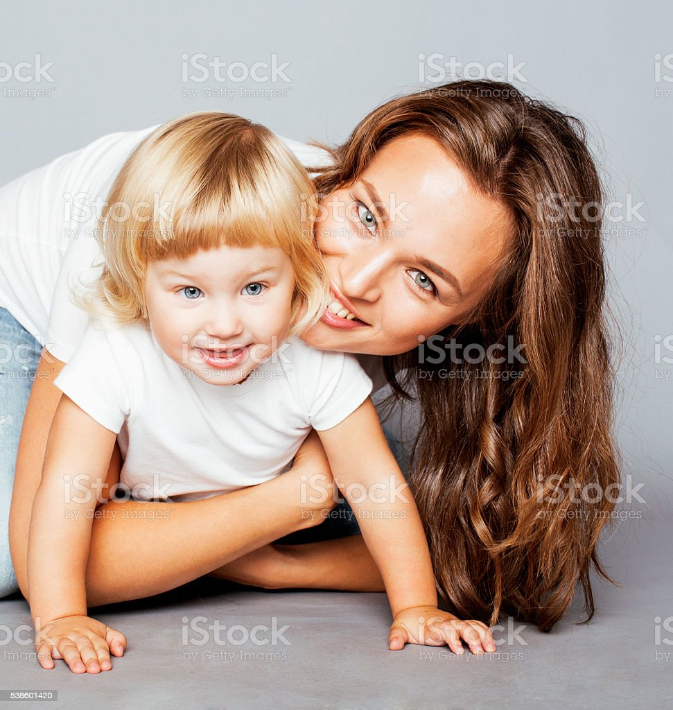 young pretty stylish mother with little cute blond daughter hugging stock photo