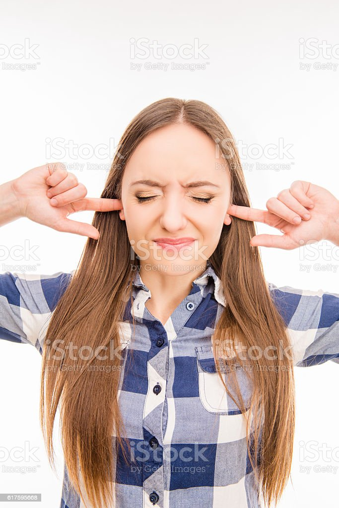 Young pretty woman covering her ears ignoring noise stock photo