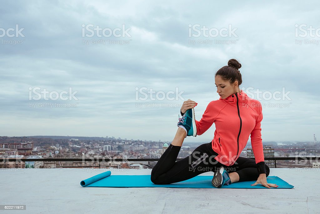 young pretty woman doing yoga stretching on the rooftop stock photo