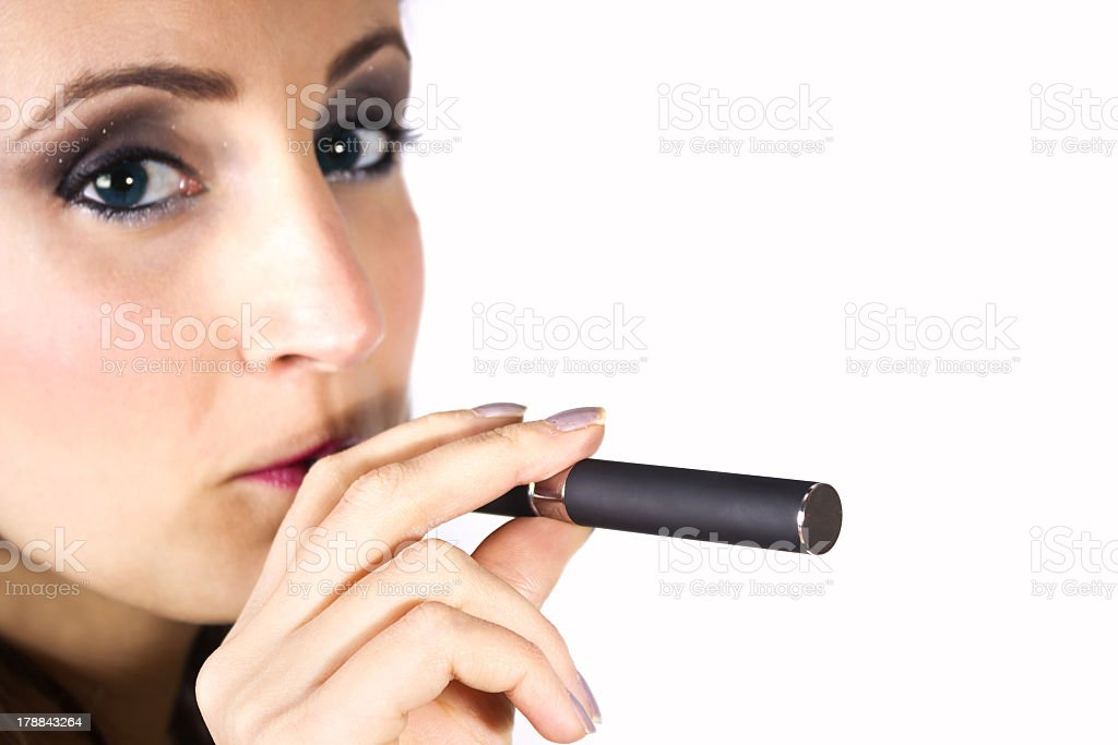 Young pretty woman enjoys her electric cigarette on white background royalty-free stock photo