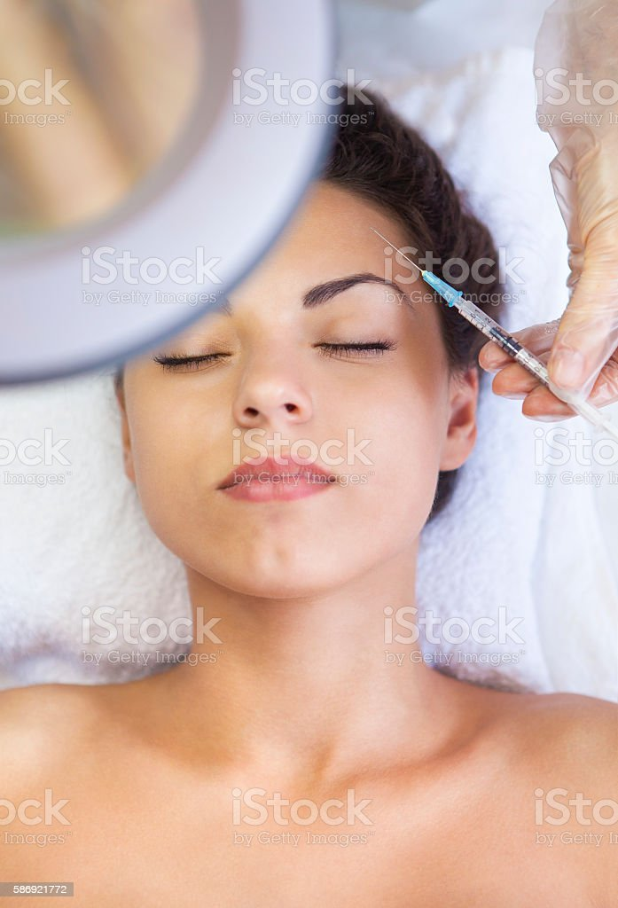 Young pretty woman getting cosmetic injection in the face stock photo