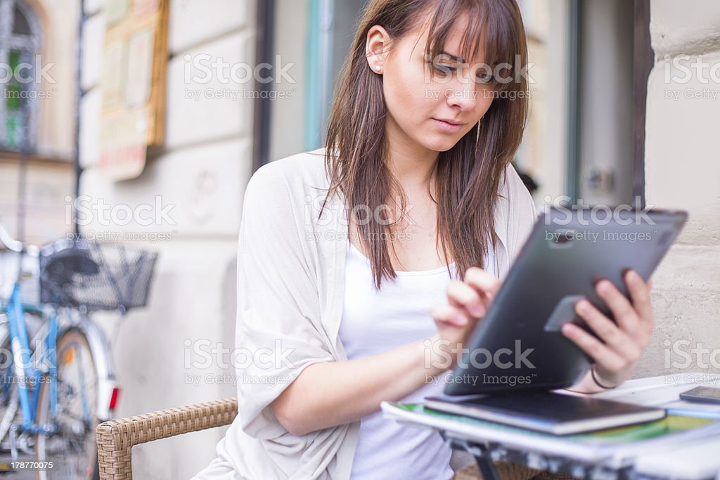 Young pretty woman holding Ipad looking away. stock photo