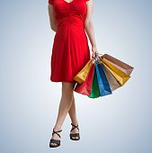 Young pretty woman is walking and holds shopping bags.