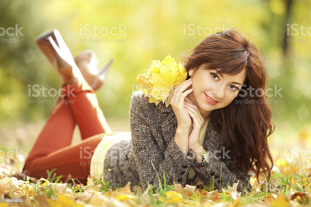 Young pretty woman resting in the autumn park royalty-free stock photo