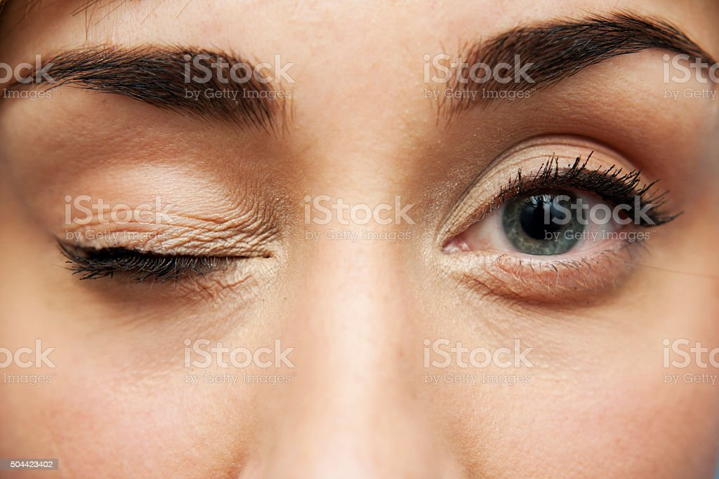 young pretty woman with closed one eye stock photo