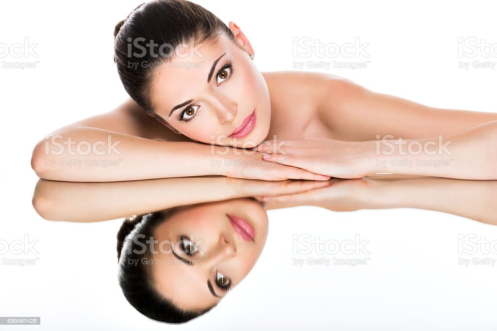 young pretty woman with healthy skin reflections in a mirror stock photo