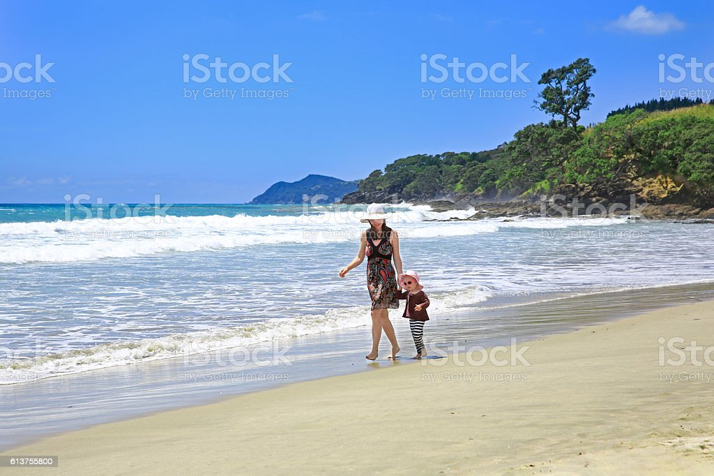 Young pretty woman with her daughter strolling along Sandy Beach stock photo