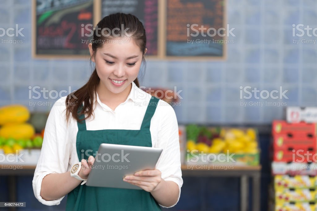 young pretty woman works in fruit store stock photo