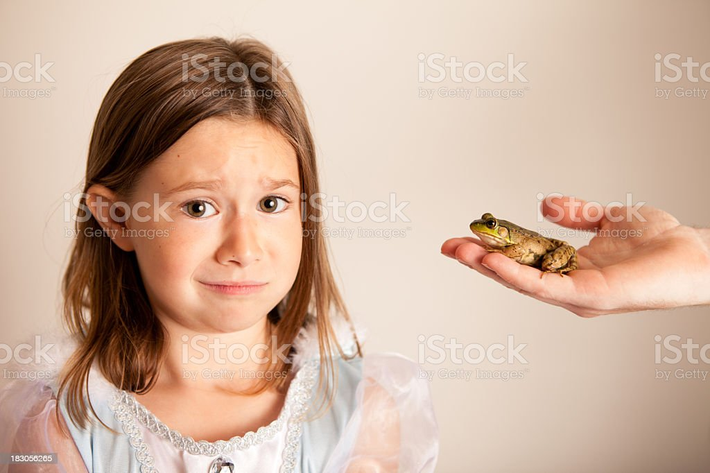 Young Princess Girl Unsure about Kissing a Frog royalty-free stock photo