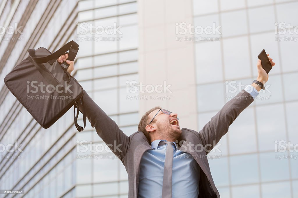 Young professional celebrating his success with hands up stock photo