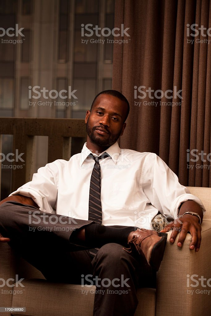Portrait of a young handsome professional black executive seated in...