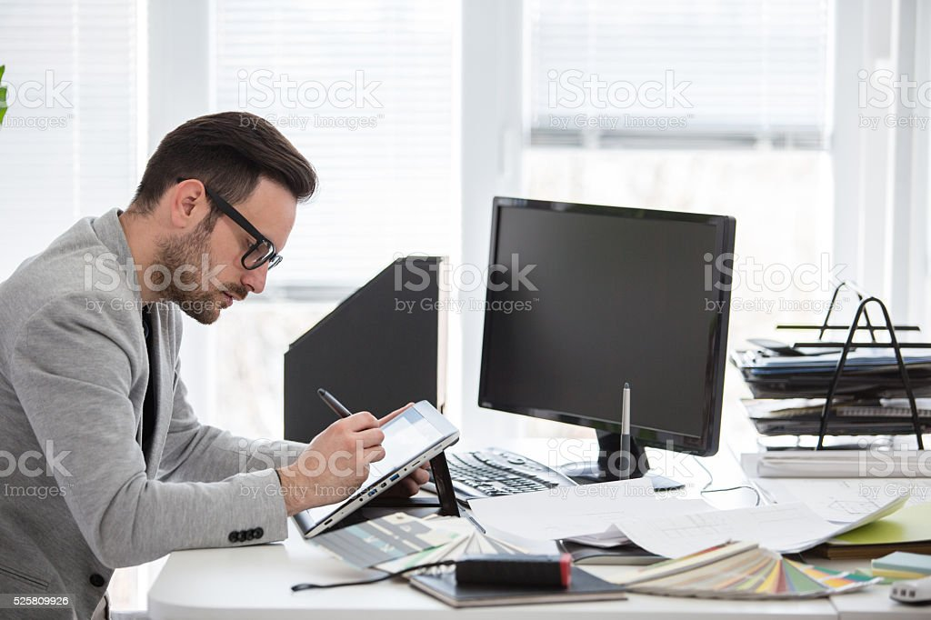 Young professional in creative office using graphic tablet stock photo