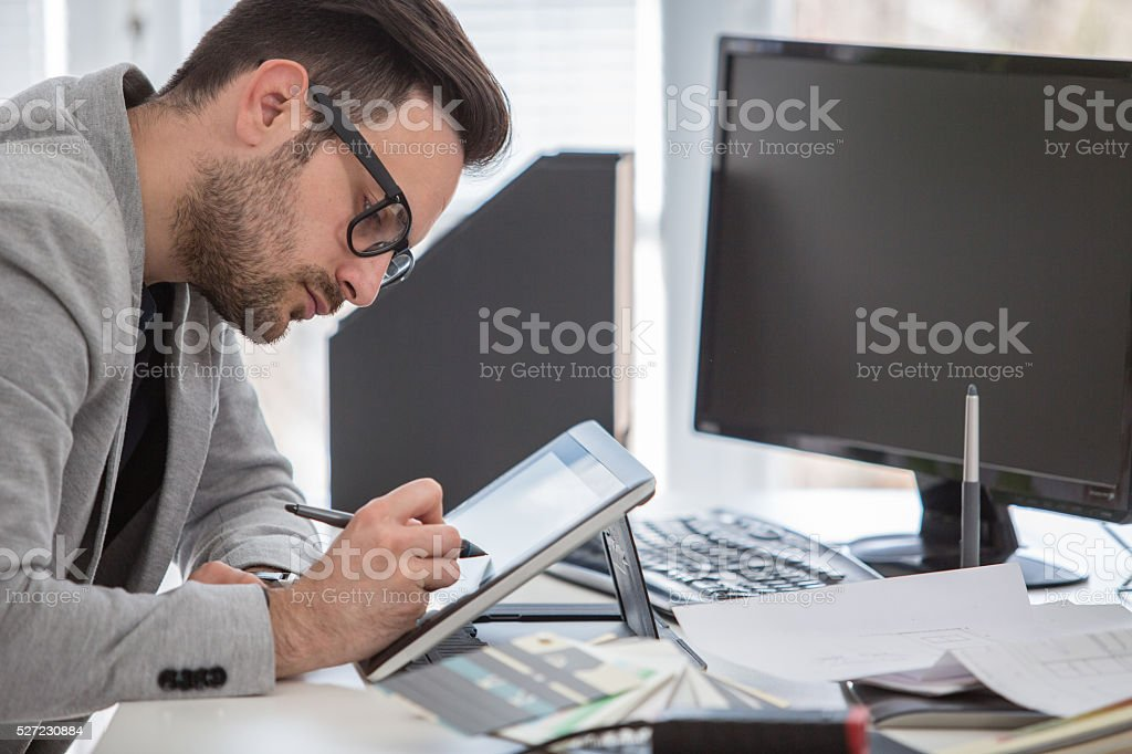 Young professional in creative office working on graphic tablet stock photo