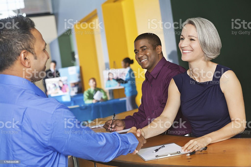 Young professional signing in, registration desk for job fair event royalty-free stock photo