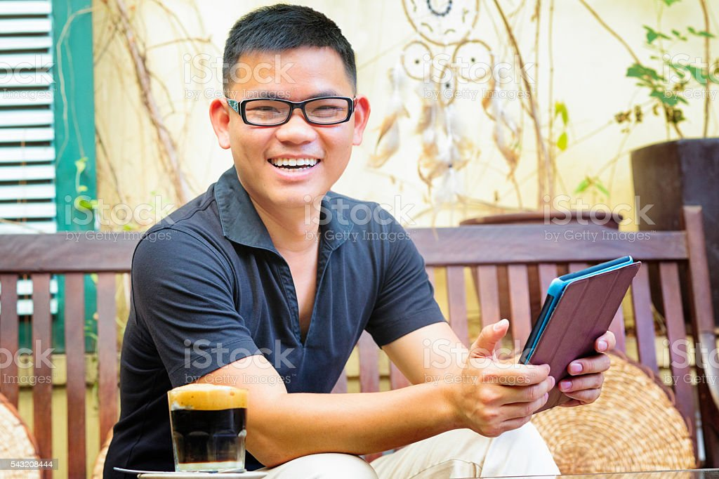 Young professional Vietnamese male portrait smiling at cafe stock photo
