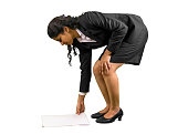 Young professional woman reaching to pick papers.