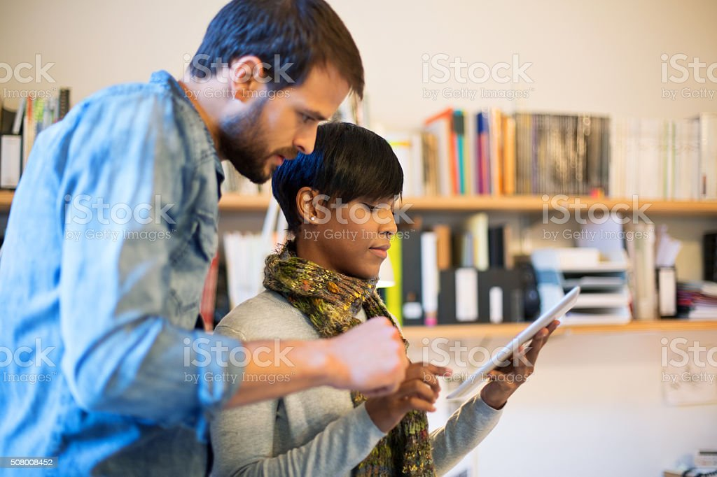 Young professionals using digital tablet at startup stock photo