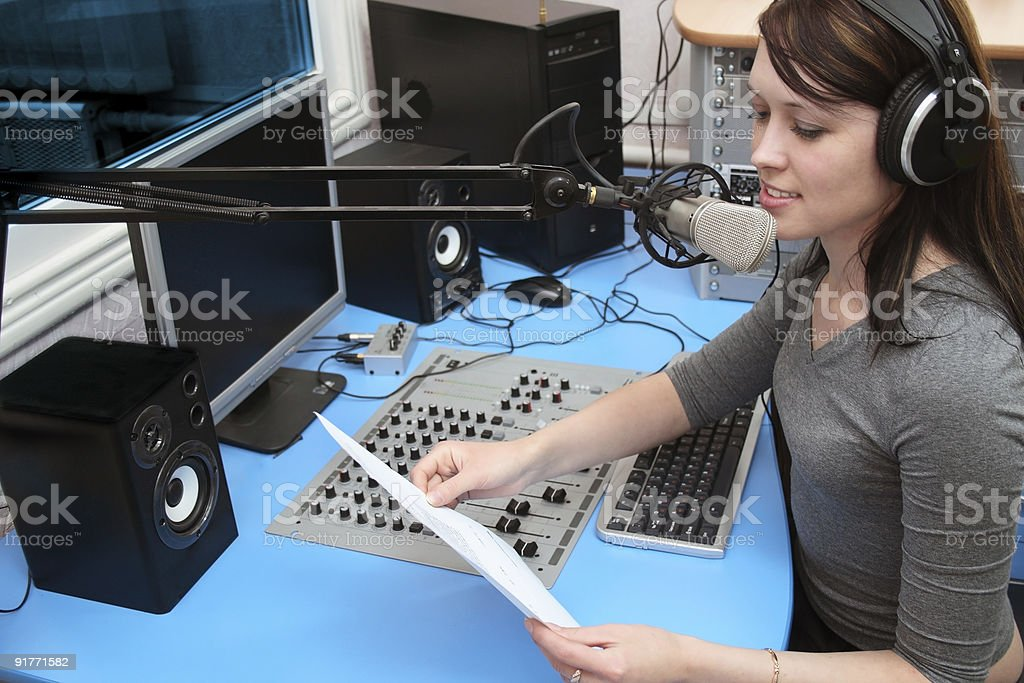 Young radio news woman in the studio stock photo