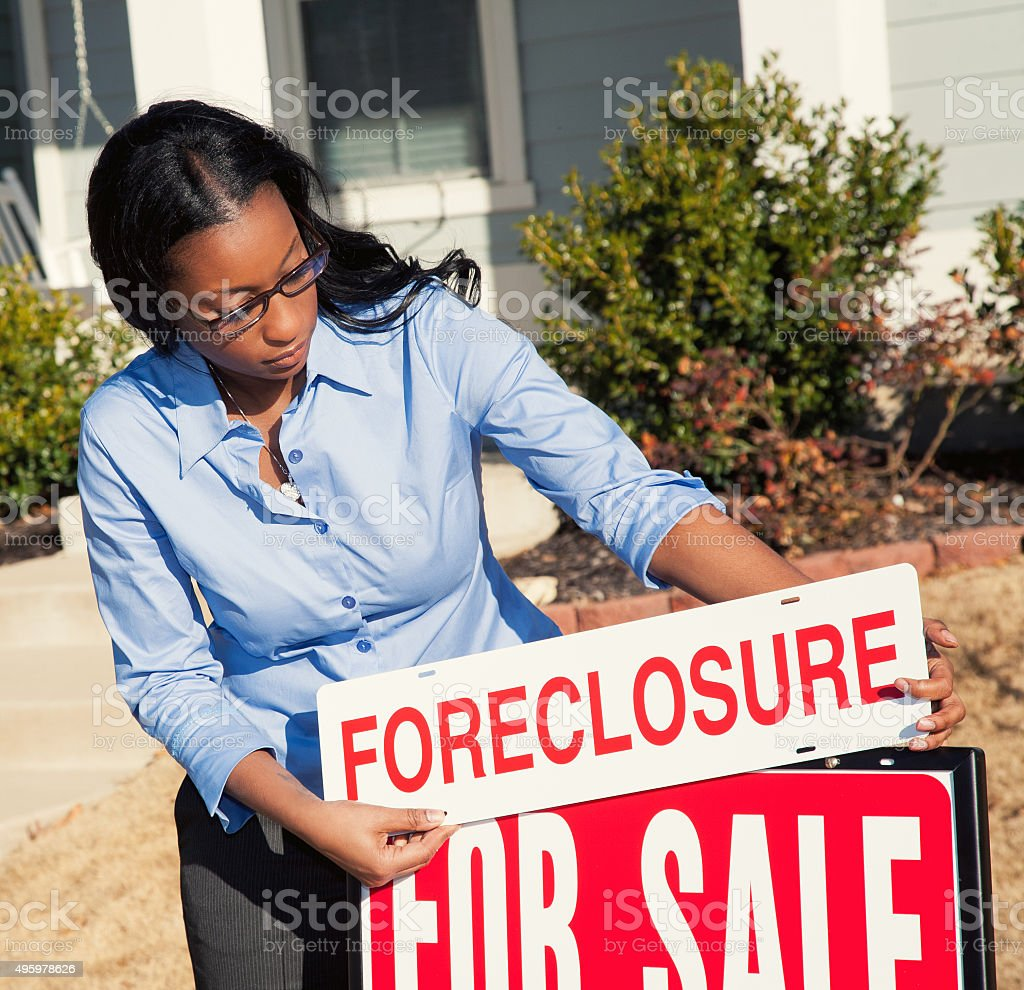 Young real estate agent placing FORECLOSURE sign in front yard stock photo