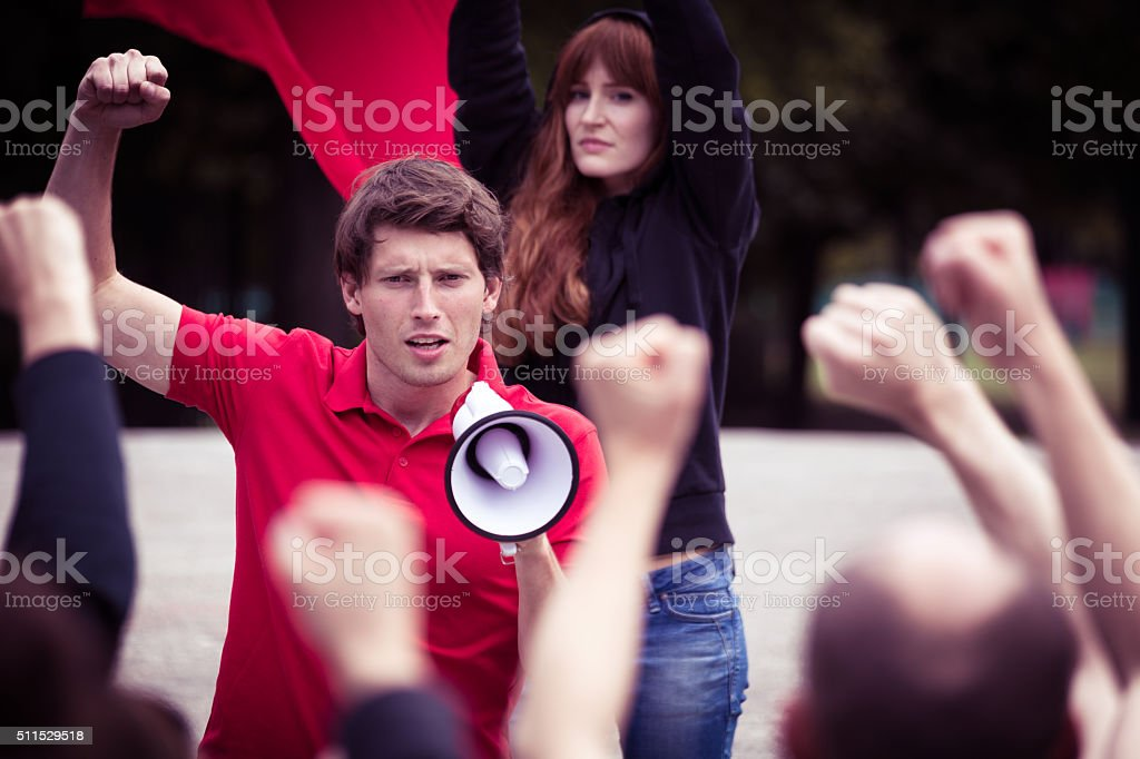Young rebellious man with megaphone stock photo