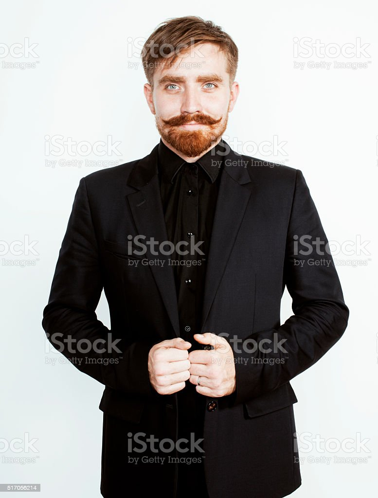 young red hair man with beard and mustache in black stock photo