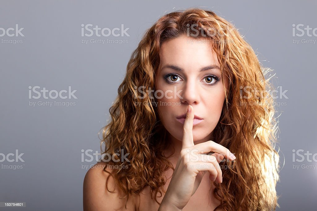 young red haired girl making a sign to be quite royalty-free stock photo