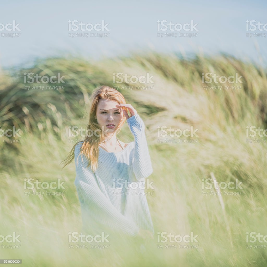 Young red haired woman in the dunes stock photo