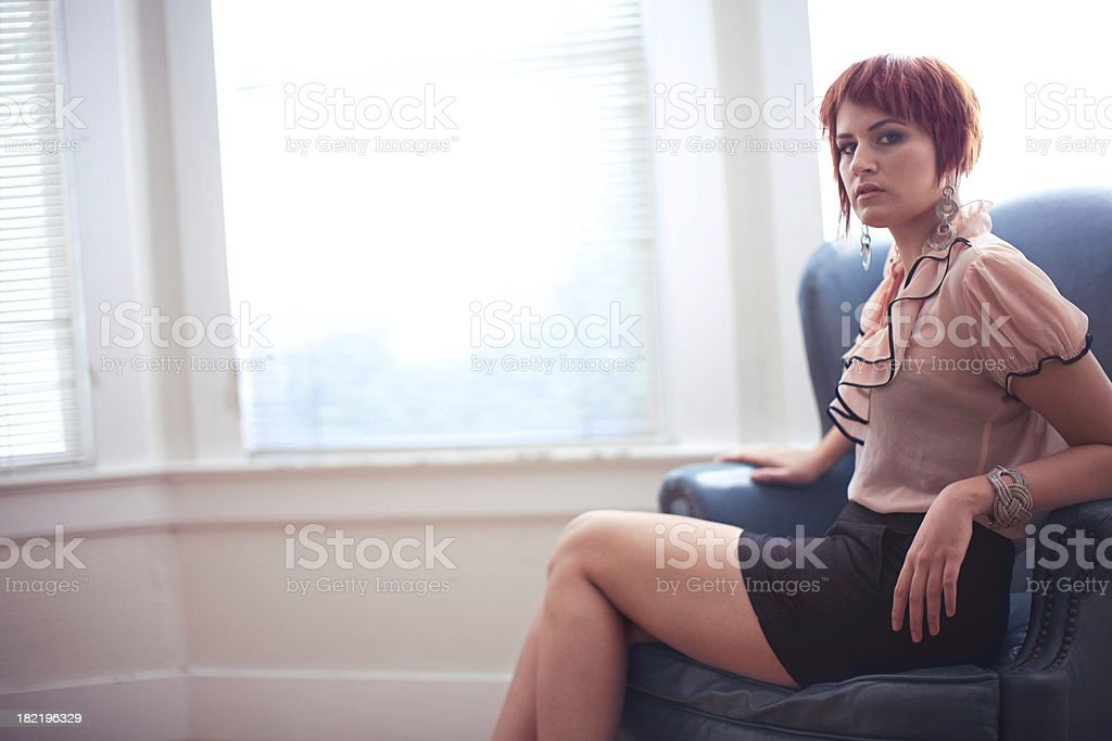 Young Red Haired Woman Reclining in a Blue Chair stock photo