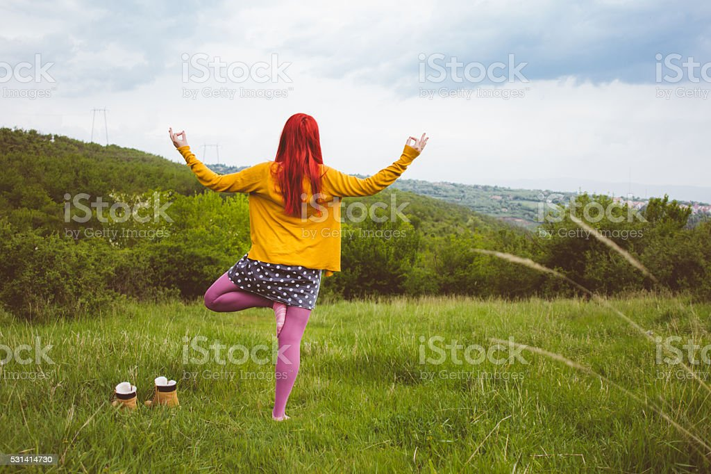 Young red hired woman is practicing yoga outdoors stock photo