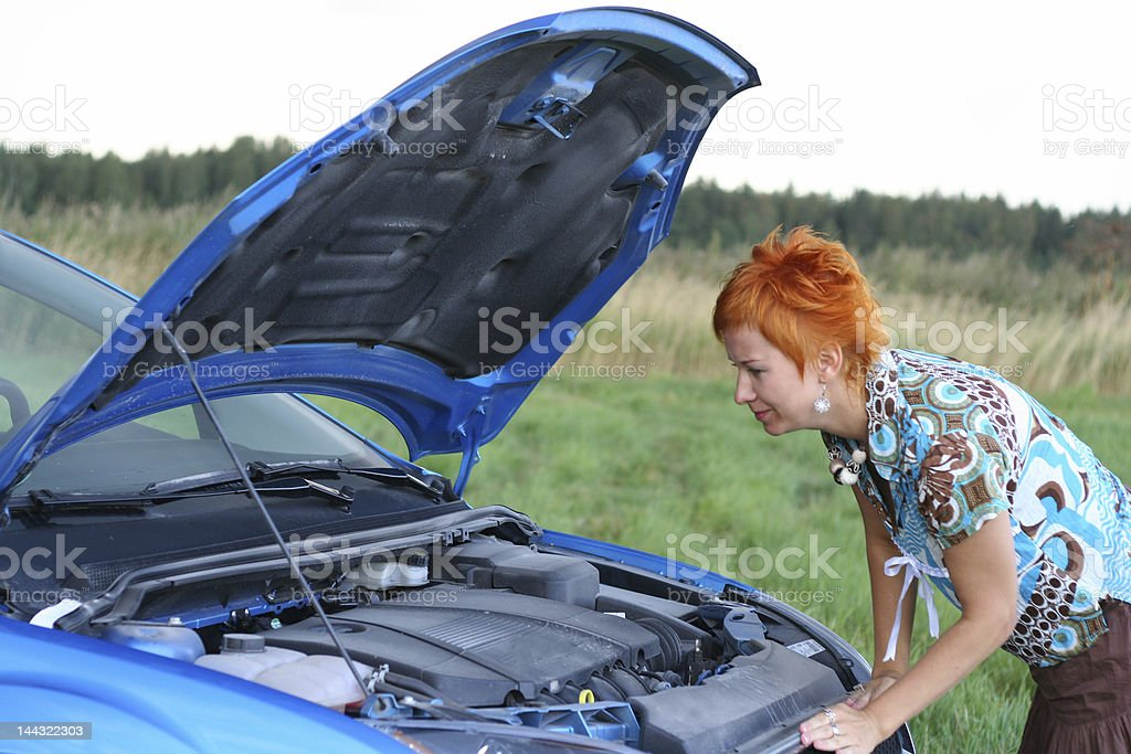 young red-haired woman with her broken car royalty-free stock photo