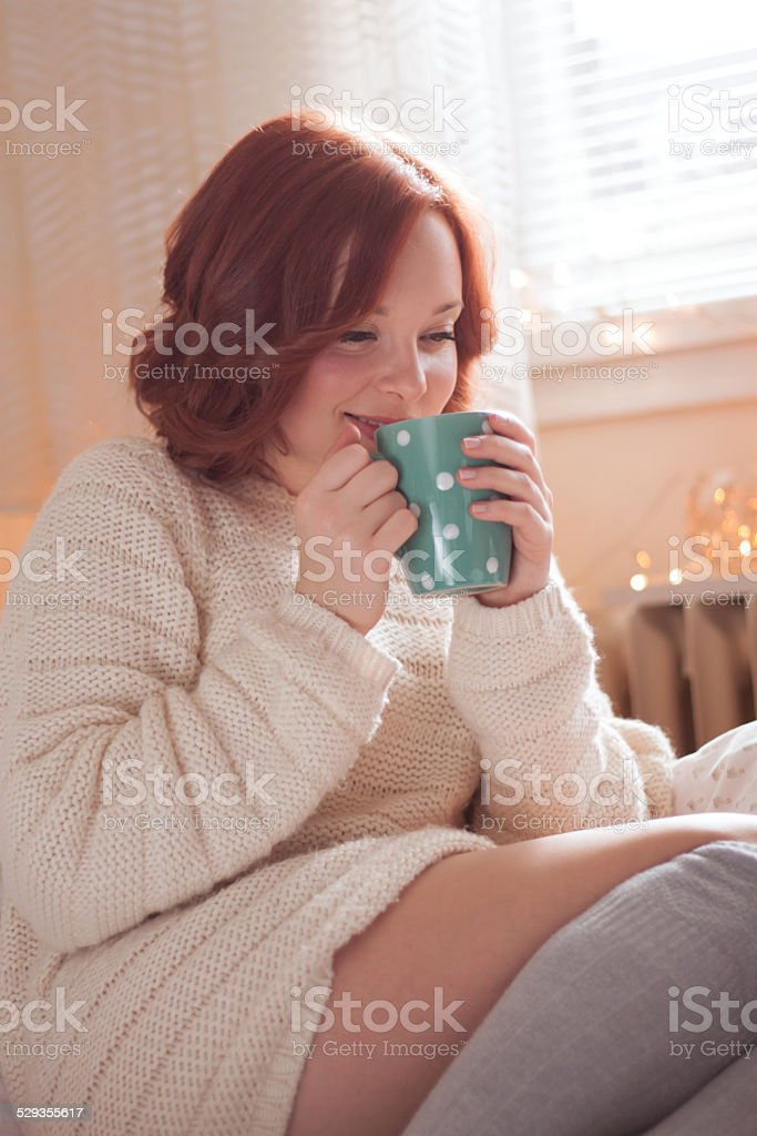 Young redhead woman in home interior. stock photo