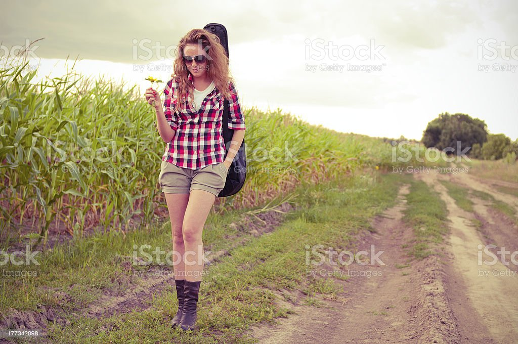 Young redhead woman with guitar passes corn field outdoors royalty-free stock photo
