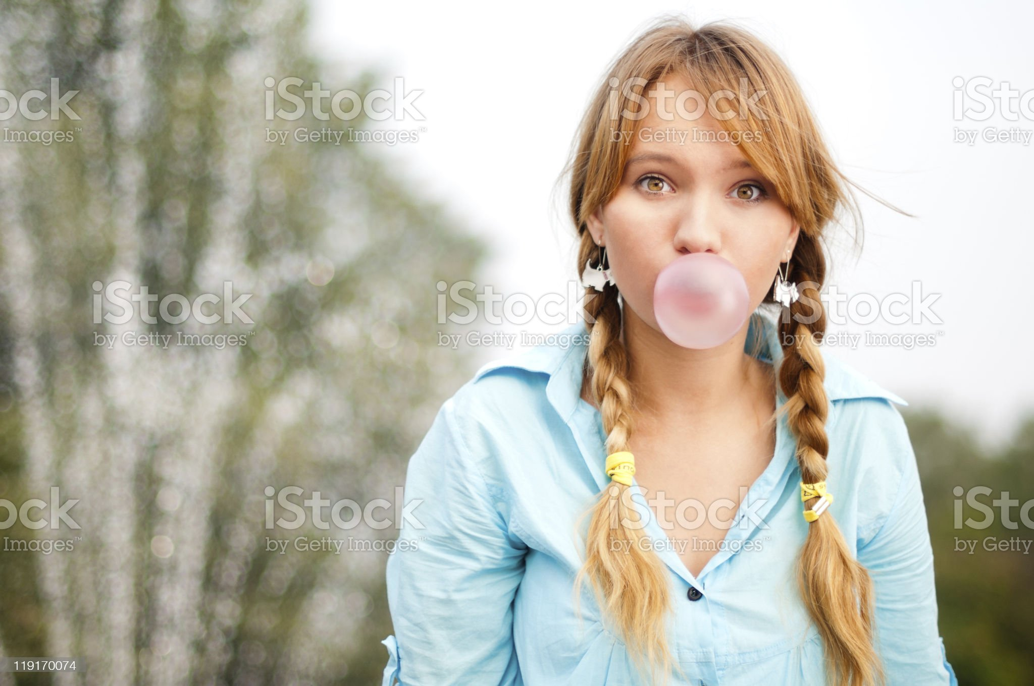 Young redheaded student in pigtail braids blows bubblegum royalty-free stock photo