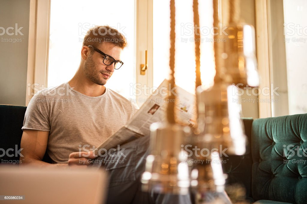 Young relaxed man reading newspaper at home. stock photo
