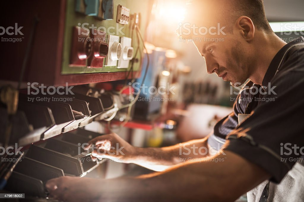 Young repairman choosing the right tool in a workshop. stock photo