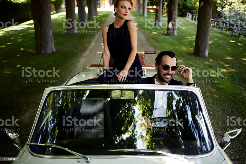 Young rich couple travel on the new white convertible stock photo