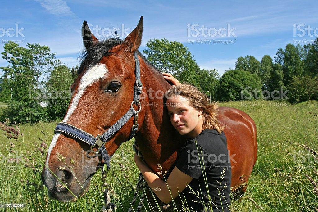 Young rider hugging her horse in a meadow, Norway royalty-free stock photo