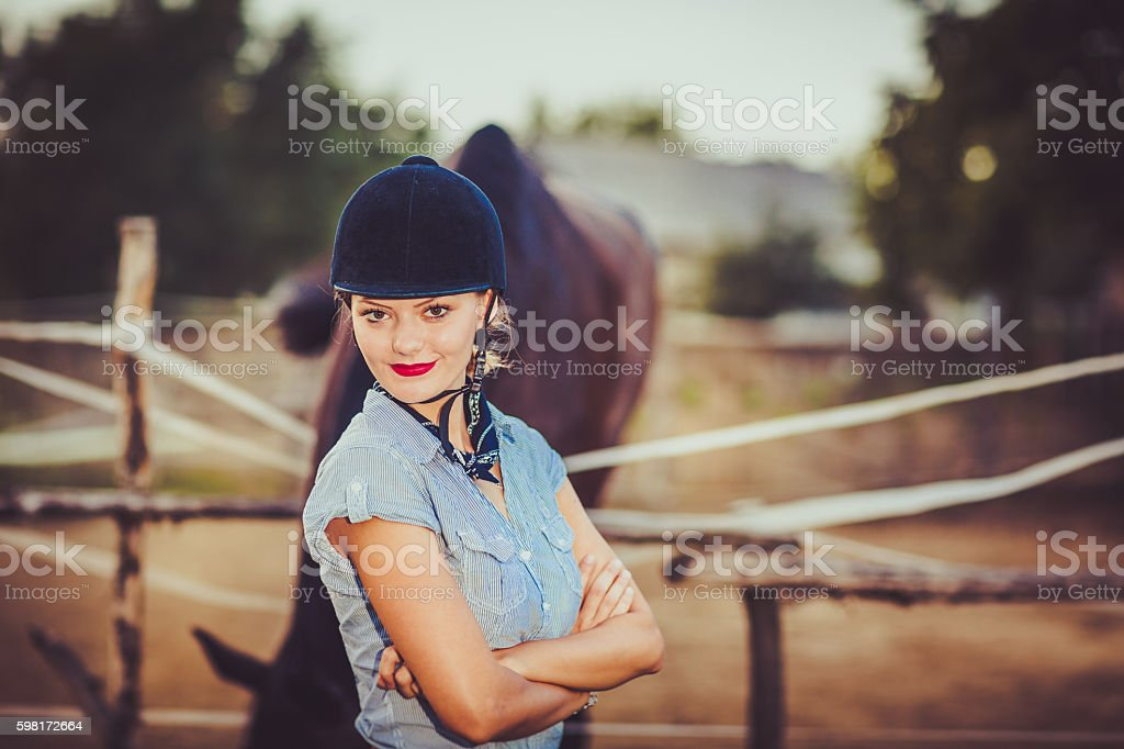 Young rider with hat and her horse stock photo