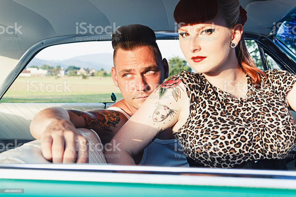 Young rockabilly couple in a car stock photo