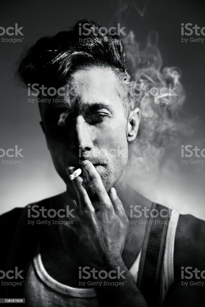 Young Rockabilly Man Smoking Cigarette, Black and White stock photo