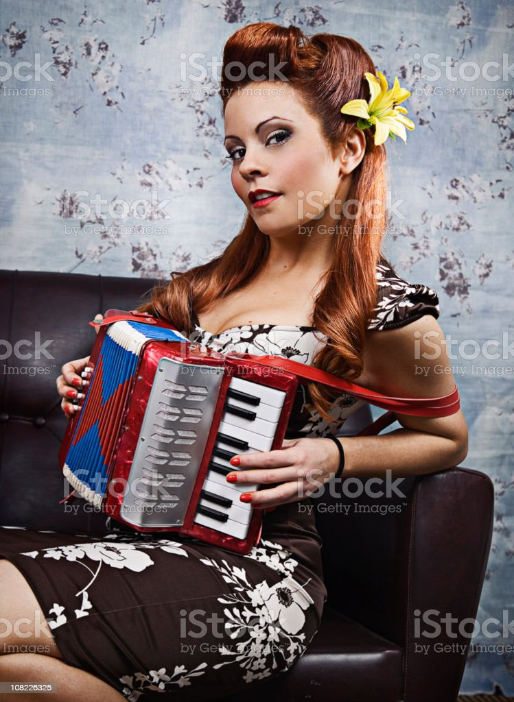 Young Rockabilly Woman Playing Accordion on Couch royalty-free stock photo