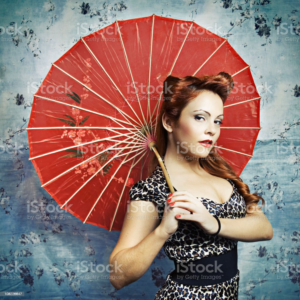 Young Rockabilly Woman Posing with Parasol Against Wall stock photo
