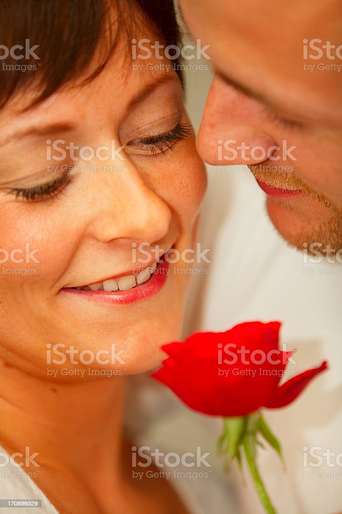 A young romantic couple enjoying the scent of a rose royalty-free stock photo