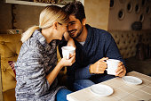 Young romantic couple flirting over coffee in cafe