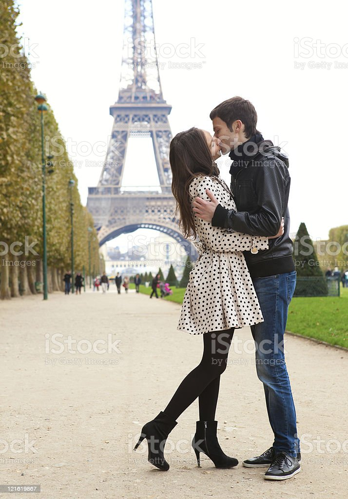 Young romantic couple kissing near the Eiffel Tower in Paris stock photo