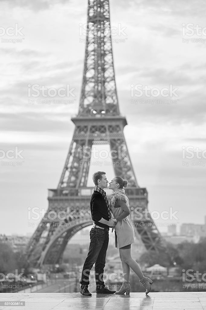 Young romantic couple near the Eiffel tower in Paris stock photo