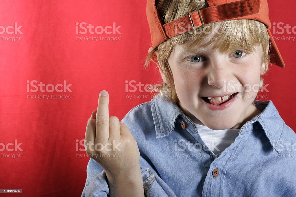 Young rude blonde boy in a cap raising his middle finger stock photo