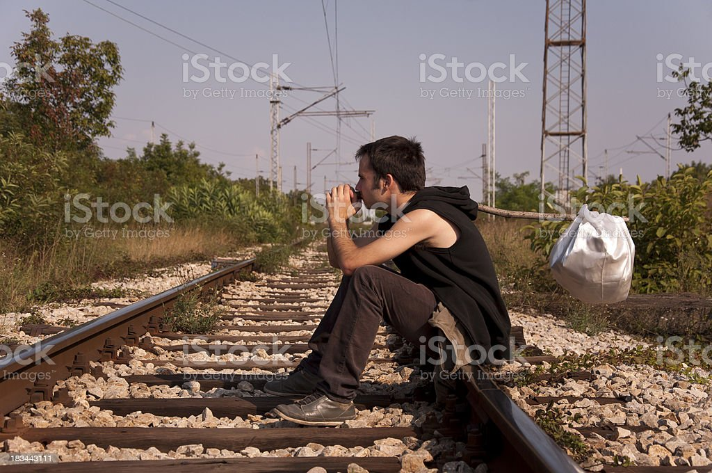 Young runaway sitting on railroad tracks royalty-free stock photo