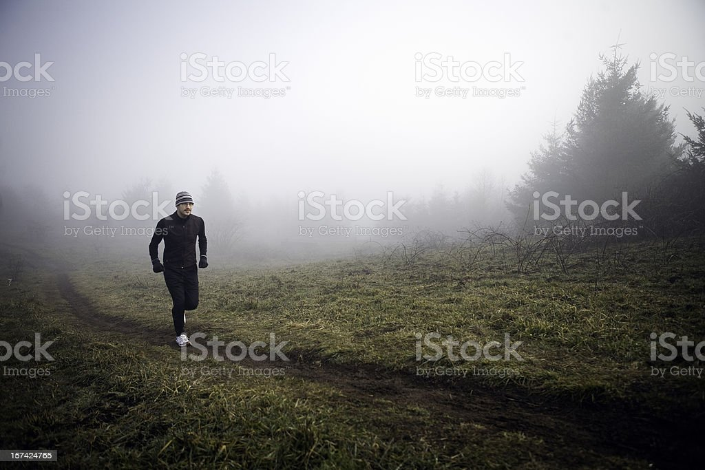 Young Runner Jogging in Morning Fog royalty-free stock photo